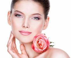 Nahaufnahmeporträt der schönen jungen Frau mit Blume nahe Gesicht.