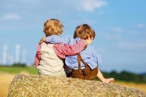 zwei kleine Kinder und Freunde sitzen auf Heuhaufen