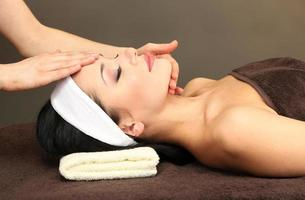 schöne junge Frau im Spa-Salon, die Kopfmassage nimmt foto