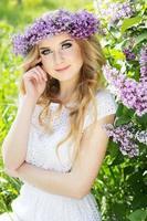 Porträt des schönen Mädchens mit Kranz aus lila Blumen