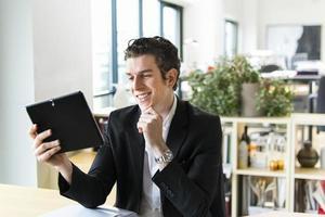 gut aussehender Mann, der auf seinem Tablett lächelt foto