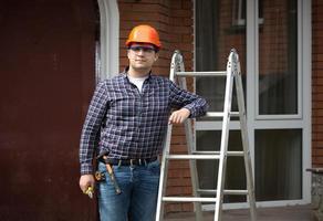 lächelnder Arbeiter im Schutzhelm, der an Metallleiter lehnt foto