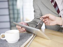 zwei junge Geschäftsleute, die beim Treffen das Touchpad benutzen foto