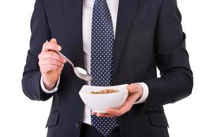 Geschäftsmann, der Frühstück mit Müslischale hat. foto