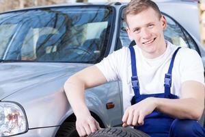 froh, dass ein Mechaniker einen Reifen wechselt foto
