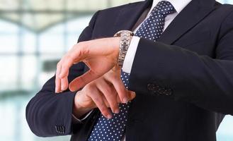 Geschäftsmann, der die Zeit auf seiner Armbanduhr überprüft. foto