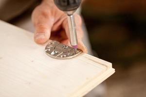 Konzentrieren Sie sich auf einen Treiber, der ein Holzbrett verschraubt foto