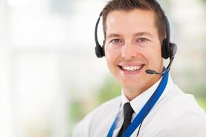 männlicher Callcenter-Mitarbeiter, der ein Headset trägt foto