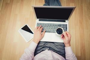Laptop und Kaffeetasse in den Händen des Mädchens sitzen foto