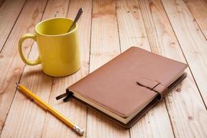 Kaffeetasse mit Notizbuch und Bleistift foto