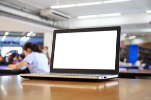Laptop mit leerem Bildschirm auf dem Tisch in der Bibliothek foto