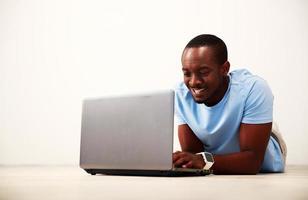 Mann auf dem Boden liegend und mit Laptop foto