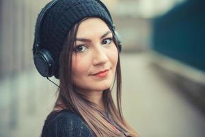 junges schönes brünettes Frauenmädchen, das Musikkopfhörer hört