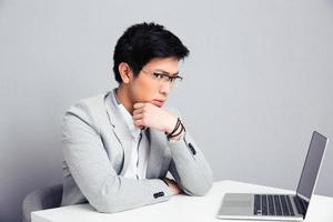 nachdenklicher Geschäftsmann, der mit Laptop am Tisch sitzt