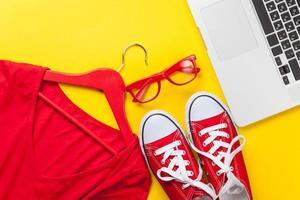 rotes Kleid und Gummischuhe mit Laptop foto