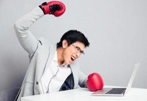 wütender Geschäftsmann, der in Boxhandschuhen am Tisch sitzt foto
