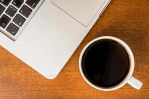 Arbeit im Büro, Kaffeetasse mit Laptop foto