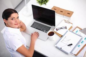 attraktive Geschäftsfrau, die auf Schreibtisch im Büro sitzt foto