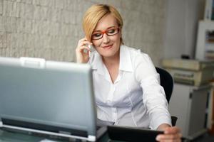 junge blonde Geschäftsfrau im Büro anrufen