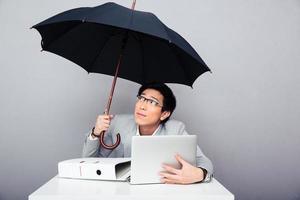 Geschäftsmann, der mit Laptop am Tisch sitzt und Regenschirm hält foto