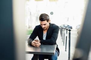 junger italienischer Junge, der ein Smartphone in einer Bar benutzt foto