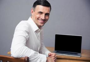 Geschäftsmann, der am Tisch mit leerem Laptopbildschirm sitzt foto