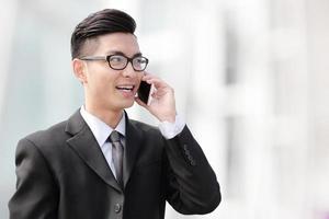 Geschäftsmann, der auf Smartphone spricht foto