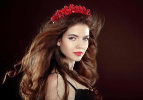 brünette junge Frau mit langen welligen wehenden Haaren und Rosenkranz