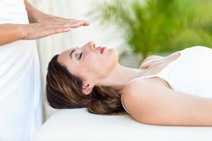 ruhige Frau, die Reiki-Behandlung erhält foto