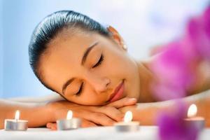 junge Frau, die in gedimmtem Kerzenlicht nach der Massage entspannt.