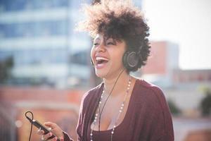 schöne schwarze afrikanische Frau des lockigen Haares, die Musik mit ihm hört