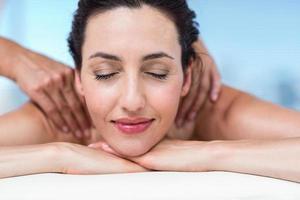 lächelnde Brünette bekommt wieder Massage foto