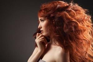 schöne Frau mit lockiger Frisur vor grauem Hintergrund foto