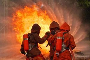 drei Feuerwehrleute, die mit einem Wasserwerfer ein Feuer löschen foto