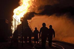 Silhouette von Feuerwehrleuten in Aktion bei Nacht foto