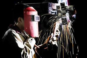 Mann mit Schutzmaske schweißt Metall und Funken foto