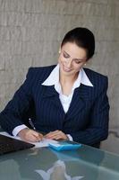 sussessful Geschäftsfrau, die schreibt und lacht foto