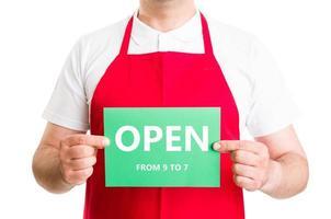 männlicher Supermarktangestellter, der 9 bis 7 Zeichen offen hält foto