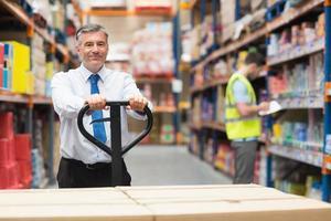 Manager zieht Wagen mit Kisten vor seinem Angestellten foto
