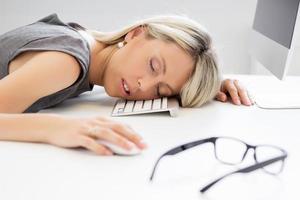 Erschöpfte Frau, die vor dem Computer schläft foto
