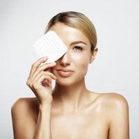 Frau reinigt ihr Gesicht foto