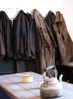 alte Arbeiteroveralls und Mäntel hingen am Ende der Schicht auf foto