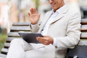schöner Mann, der auf der Bank sitzt foto