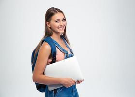 Studentin, die Laptop hält und Kamera betrachtet foto