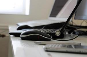 Büroarbeitsplatz mit Laptop, Maus und Handy foto