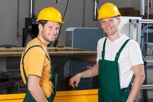Arbeiter stehen neben der Maschine foto