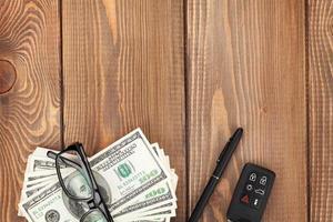 Geld, Brille und Autoschlüssel auf Holztisch foto