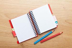 Bürotisch mit leerem Notizblock und bunten Stiften foto