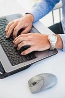 Nahaufnahme der Zeiger mit Armbanduhr, die auf Laptop schreibt foto