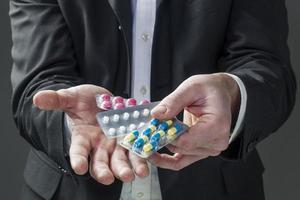 Geschäftsmann, der Pillen im Büro nimmt